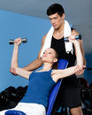 Trainer helps woman to exercise with weights Royalty Free Stock Images