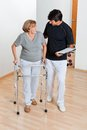 Trainer looking at senior woman using walker full length of a holding clipboard and women Royalty Free Stock Image