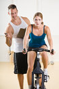 Trainer timing woman on stationary bicycle Royalty Free Stock Photo
