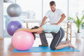 Trainer working with woman on exercise ball Royalty Free Stock Photo