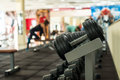 Training apparatus in gym hall dumbbells hanging on metal rack people on background Stock Photos
