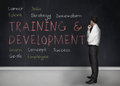 Training and development terms written on a blackboard businessman looking at Royalty Free Stock Photos