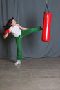 Training woman kicks punching bag Royalty Free Stock Photography