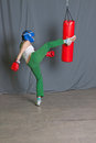 Training woman kicks punching bag Stock Image