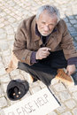 Tramp depressed senior man in dirty wear sitting on the floor outdoors and smoking Royalty Free Stock Photo