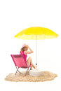Tranquil beach with woman in chair pink and under yellow parasol isolated over white background Royalty Free Stock Photography