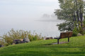 Tranquil bench on the foggy shore Stock Image