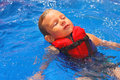 Tranquil kid in vest floating on her back at the pool aqua park Royalty Free Stock Image