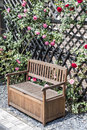 Tranquil relax romantic garden bench surrounded red and pink roses blossom bushes Royalty Free Stock Photo