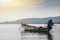 Tranquil scenery with traditional asian boat in sea during sunset Royalty Free Stock Photo