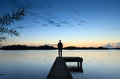 Tranquil sunset man standing on a small jetty looking over a dutch lake during a calm blue Royalty Free Stock Photos