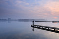 Tranquil view man standing on a jetty looking over a lake Royalty Free Stock Image