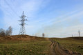 Transmission tower on the hill against blue sky