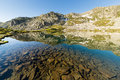 Transparent alpine lake high altitude mountain at sunrise in idyllic uncontaminated environment with clean and water location Stock Images