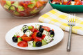 Transparent glass bowl and plate with Greek salad, fork Royalty Free Stock Photo