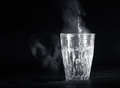 Transparent glass cup with swell the boiling water into it. The vapor from the top. Black background. Royalty Free Stock Photo