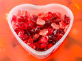 Transparent heart shape vase bowl filled with colored red heart shape jellies red hearts background close up Royalty Free Stock Image
