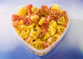Transparent heart shape vase (bowl) filled with colored (red, yellow an orange) heart shape pasta, colored degradee background Royalty Free Stock Photo