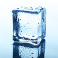 Transparent ice cube with reflection on blue glass with water drops Royalty Free Stock Photo
