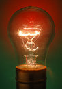 Transparent lightbulb illuminated on red and green background. Royalty Free Stock Photo