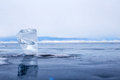 A transparent piece of ice on the surface of the blue frozen lake Baikal Royalty Free Stock Photo