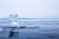 A transparent piece of ice on surface of blue lake Baikal Royalty Free Stock Photo