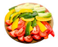 Transparent plate with sliced red tomatoes, yellow and green capsicums and cucumbers Royalty Free Stock Photo