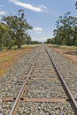 Transport a railway track heading off into the distance with trees and clouds Royalty Free Stock Image