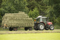 Transportation of bales of hay with a red tractor and flat car Stock Photography