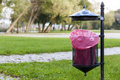 Trash basket with pink plastic bag standing in park in the background of trees metal roof of graffiti Royalty Free Stock Image