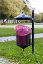 Trash basket with pink plastic bag standing in park in the background of trees metal roof of graffiti Royalty Free Stock Photo