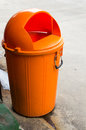 Trashcan orange color on cement floor Stock Photo