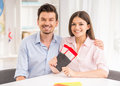 Travel agency young happy couple sitting at tourist and holding tickets Royalty Free Stock Images