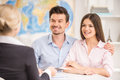 Travel agency young happy couple sitting at tourist and talking with agent Royalty Free Stock Images