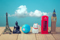 Travel around the world concept. Souvenirs from around the world on wooden table over blue sky background
