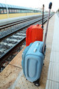 Travel bags stands on platform near railway tracks Royalty Free Stock Image