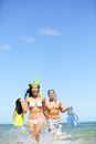 Travel beach vacation people happy couple fun having in ocean water on tropical with snorkeling fins equipment running Stock Images