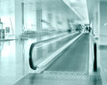 Travel concept escalator inside modern airport terminal image in blue colors with blur Royalty Free Stock Photo