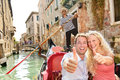 Travel concept happy couple in venice gondola giving thumbs up hand sign excited looking at camera romantic young beautiful on Stock Photos