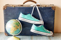 Travel concept with holiday suitcase, shoes and globe Royalty Free Stock Photo