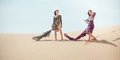 Travel concept. Two gordeous women sisters traveling in desert. Arabian Indian movie stars. Royalty Free Stock Photo
