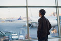 Travel concept with young man in airport interior with city view and a plane flying by. Royalty Free Stock Photo