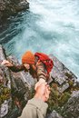 Travel couple helping hand holding together on rocks over river