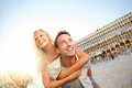 Travel couple in love having fun venice romance laughing doing piggyback ride italy on piazza san marco happy young Stock Images
