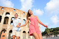 Travel couple in rome by colosseum running fun and romantic holding hands italy happy lovers on honeymoon sightseeing having Stock Image