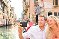 Travel couple in venice on gondole ride romance boat happy vacation holidays romantic young beautiful taking selfie Royalty Free Stock Photo