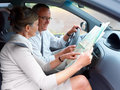 Travel - Happy couple looking at map in car Stock Images