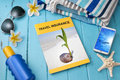 Travel insurance a tropical still life with brochure phone sunscreen sunglasses beach towel and starfish Stock Photography