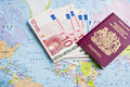 Travel passport and money resting on a map of the world Stock Photos