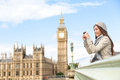 Travel tourist in london sightseeing taking photos photo pictures near big ben woman holding smart phone camera smiling happy near Royalty Free Stock Images